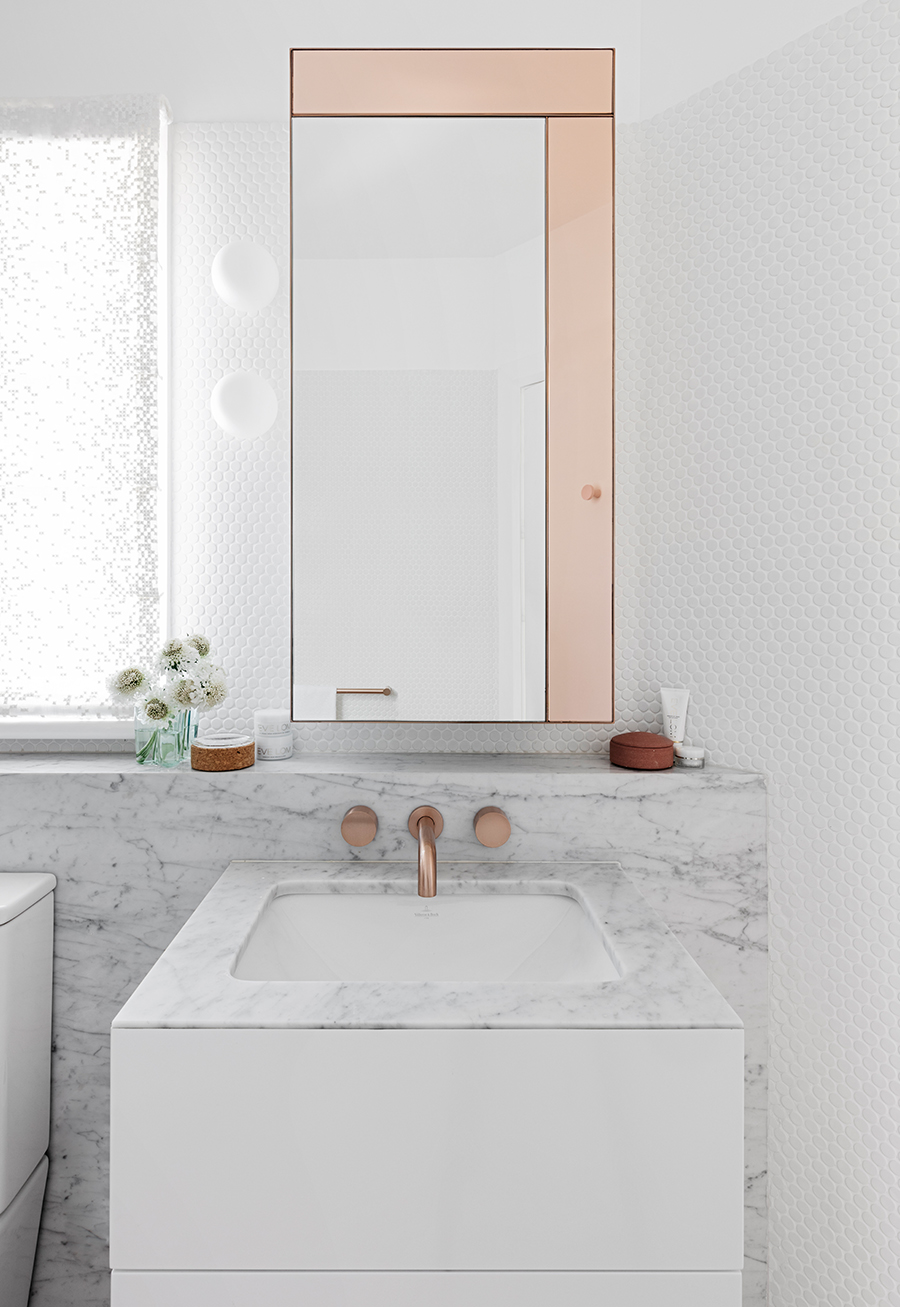 Pink gold mirror and tap in marble bathroom
